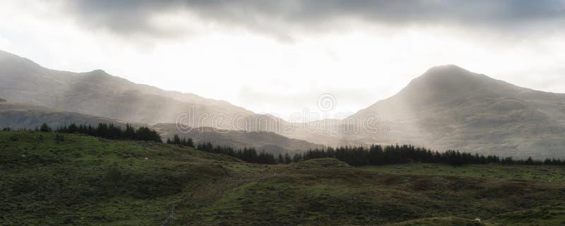 Alba del paesaggio di panorama sopra le montagne nebbiose distanti con il sole fotografie stock