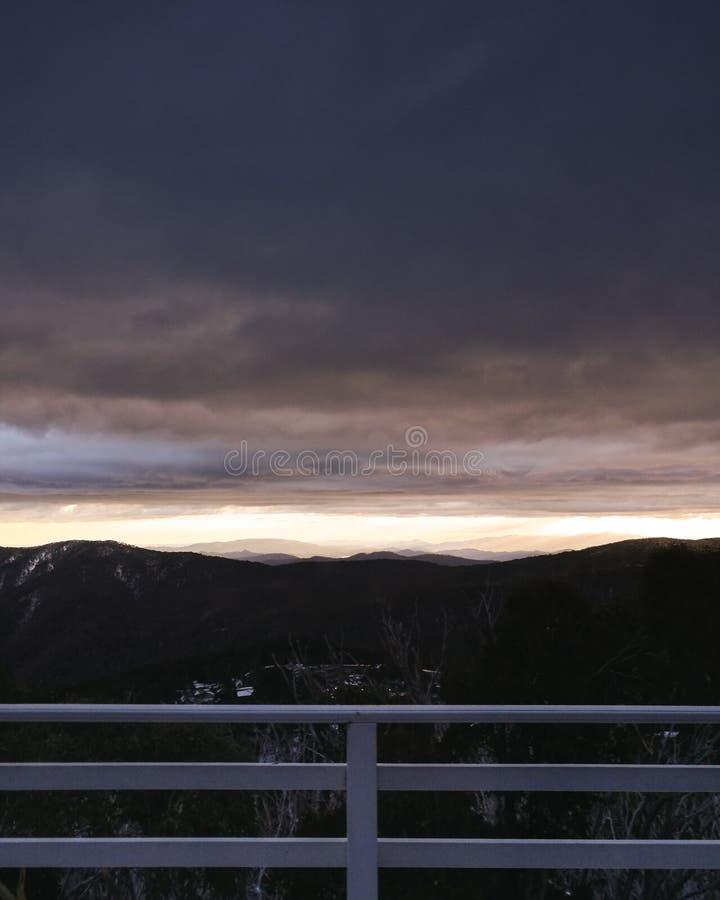 Alba di mattina sopra le montagne distanti dal balcon della casetta dello sci fotografia stock libera da diritti