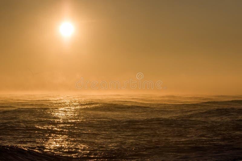Alba di vista sul mare Bello sole nebbioso di mattina sopra il mare con il generatore eolico del fondo fotografia stock libera da diritti