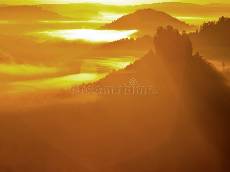 Alba dorata maestosa in una bella montagna La roccia dell'arenaria è aumentato dal fondo nebbioso della valle dell'oro immagine stock libera da diritti