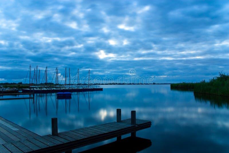 Alba e nubi sopra un lago immagine stock
