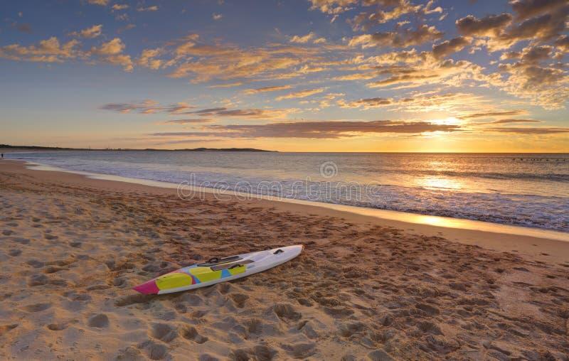 Alba e paddleboard della spiaggia su litorale immagini stock libere da diritti