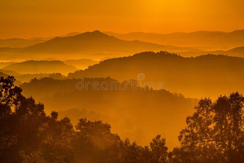Alba in grandi montagne fumose immagine stock