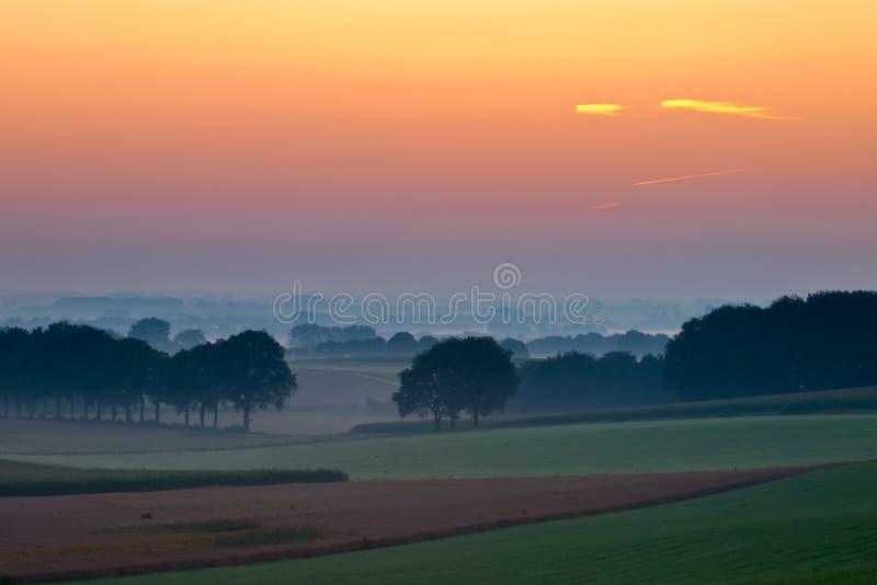 Alba magica sopra il paese agricolo del pendio di collina fotografia stock