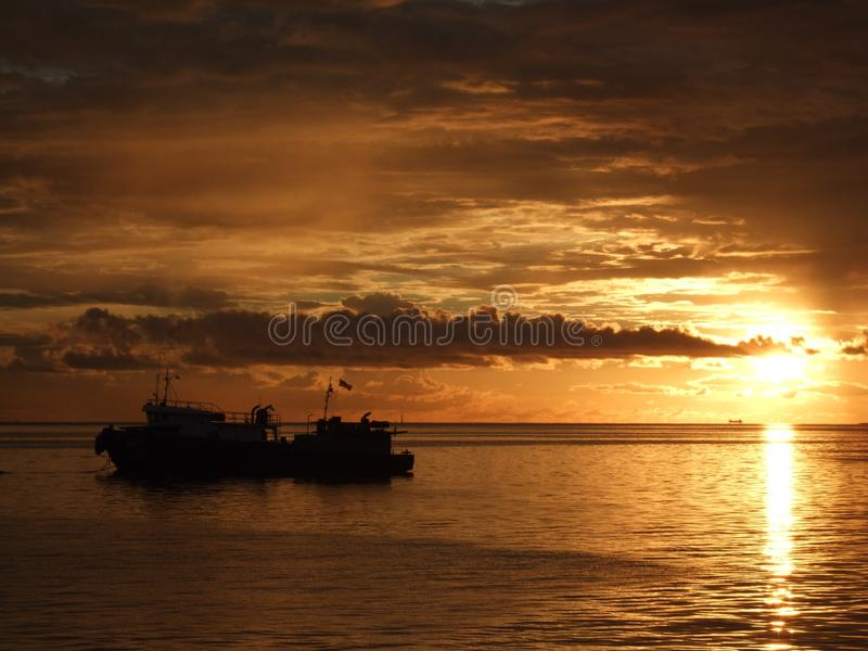 Alba in mare che mostra un'incandescenza gialla calda sui cieli e su un peschereccio fotografie stock