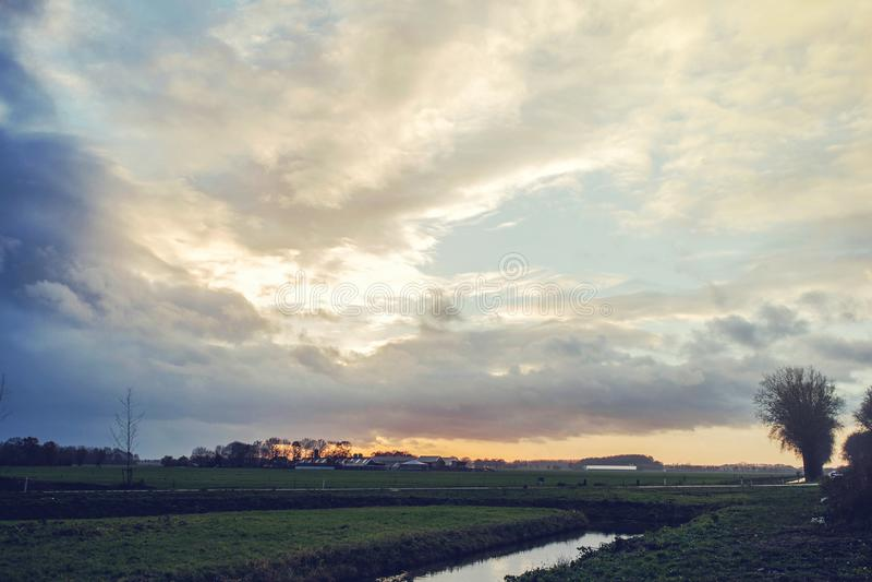 Alba naturale di tramonto sopra il campo o il prato Cielo drammatico luminoso e terra scura Paesaggio della campagna sotto scenic immagini stock libere da diritti