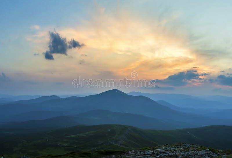 Alba o tramonto fantastica sopra la cresta verde della montagna coperta di nebbia blu densa Sole arancio luminoso che si alza in  immagini stock