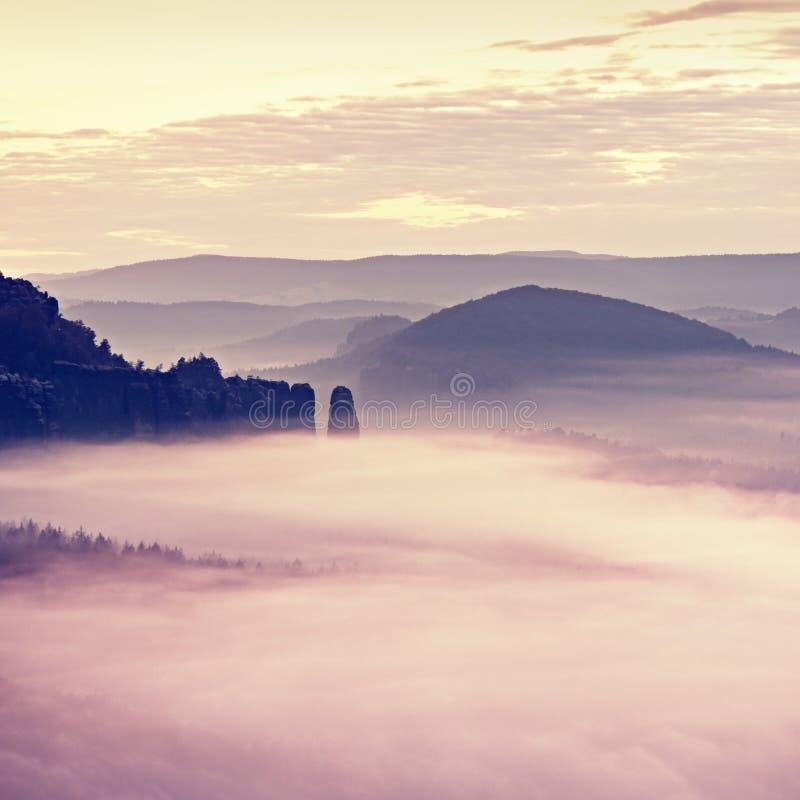 Alba rosa nel paesaggio collinoso Mattina nebbiosa di autunno in belle colline rocciose immagine stock