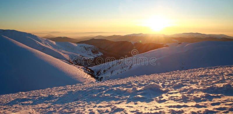 Alba in sole luminoso delle montagne nevose di inverno sul congelato su immagini stock libere da diritti