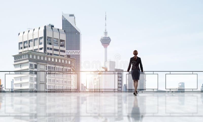 Alba sopra i grattacieli e la donna di affari che affrontano nuovo giorno immagini stock