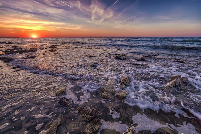 Alba sopra il mare con il mosso dell'acqua fotografie stock libere da diritti