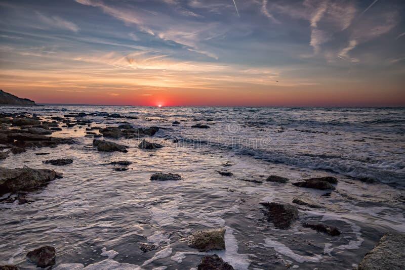 Alba sopra il mare con il mosso dell'acqua fotografia stock libera da diritti
