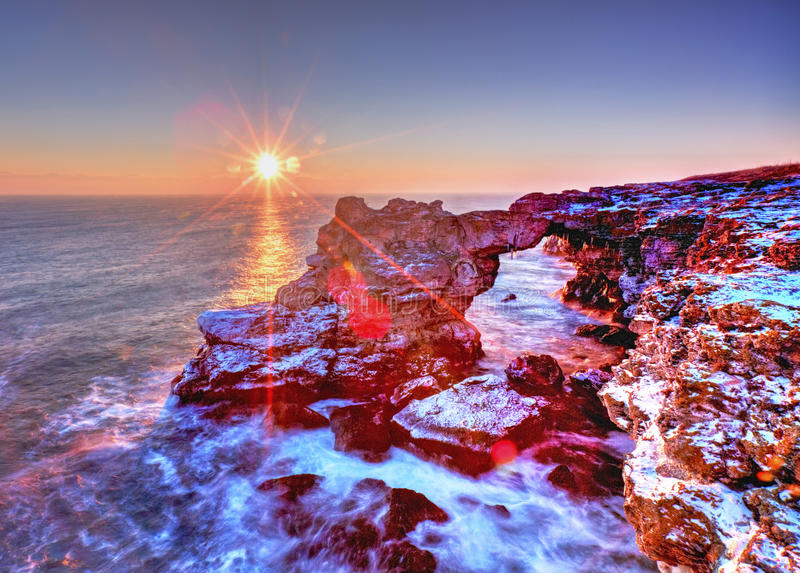 Alba sopra il mare e la riva rocciosa immagine stock libera da diritti