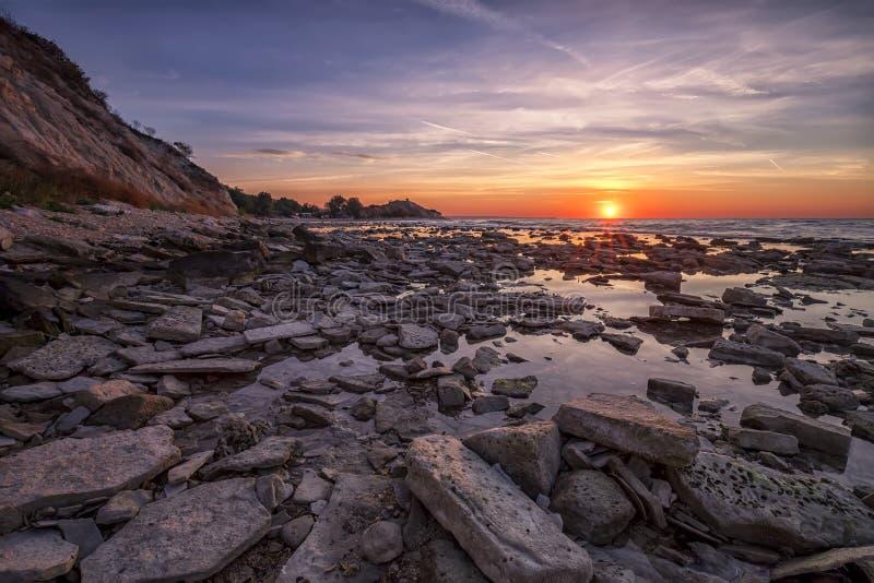 Alba sopra il mare roccioso della costa immagini stock
