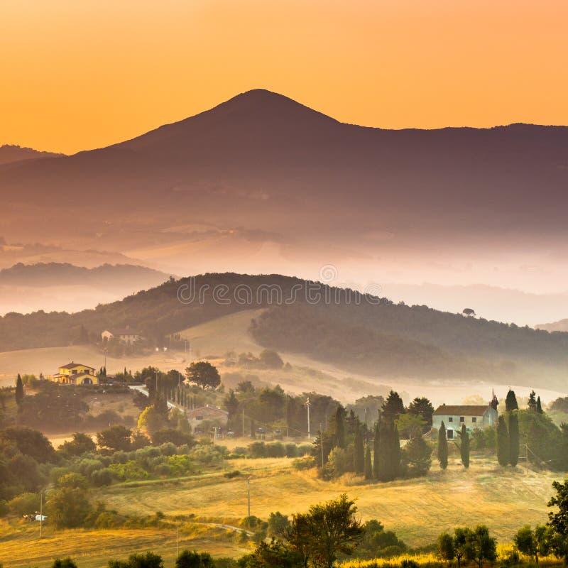 Alba sopra il villaggio nebbioso della Toscana fotografia stock