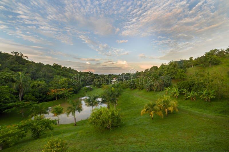 Alba sopra l'azienda agricola tropicale con lo stagno ed il cielo drammatico fotografia stock