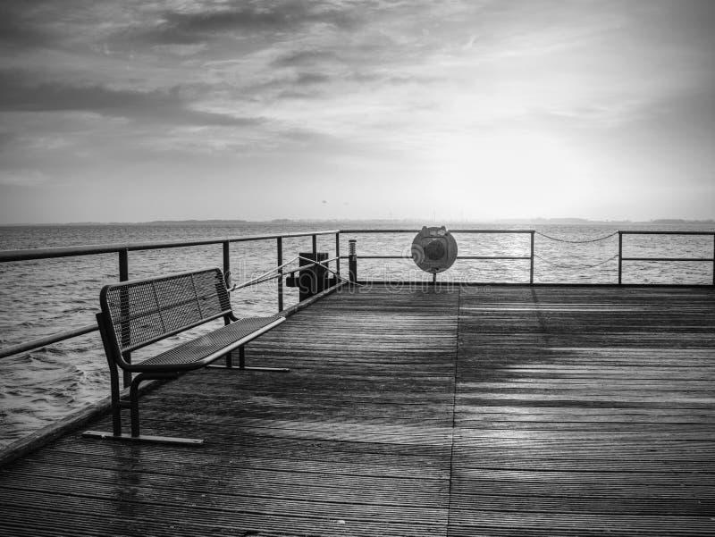 Alba sopra l'oceano Pilastro di legno vuoto alla mattina variopinta immagine stock