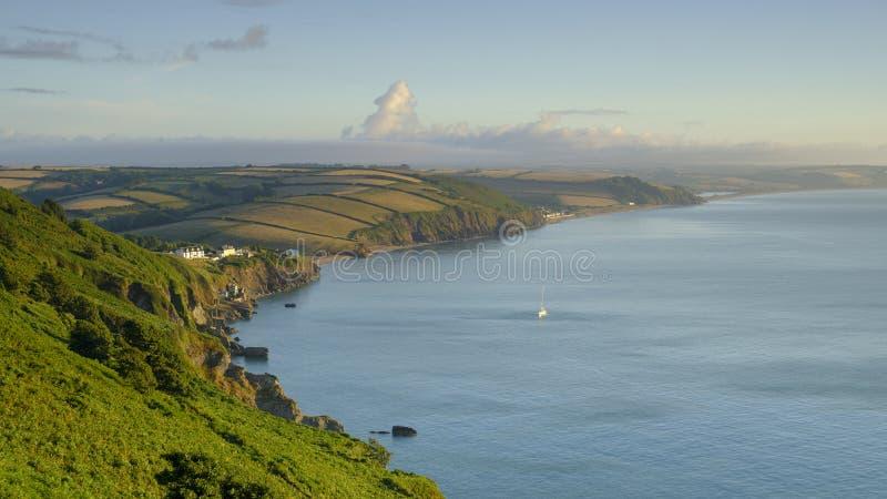 Alba sopra la baia di inizio vicino alla casa leggera che guarda lungo la costa verso le sabbie di Slapton e di Beesands con il r fotografie stock