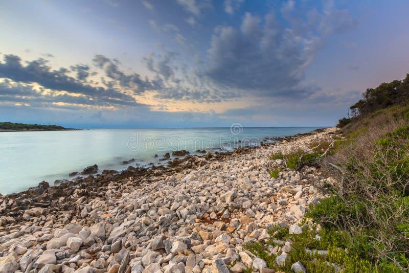 Alba sopra la costa rocciosa su Cres immagini stock