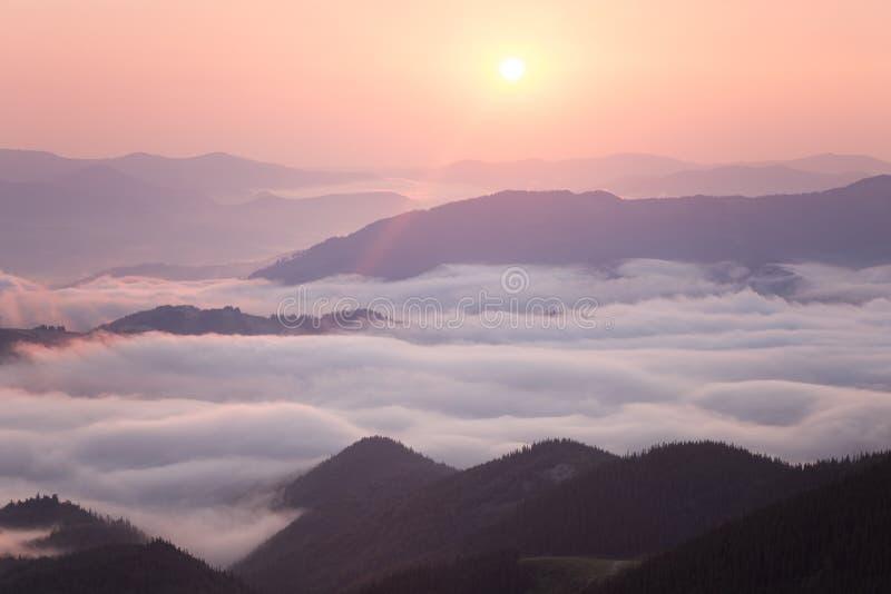 Alba sopra la cresta nuvolosa della montagna fotografia stock