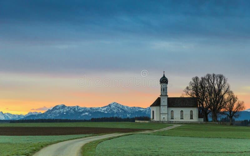 Alba sopra la vecchia cappella nel campo verde fotografie stock
