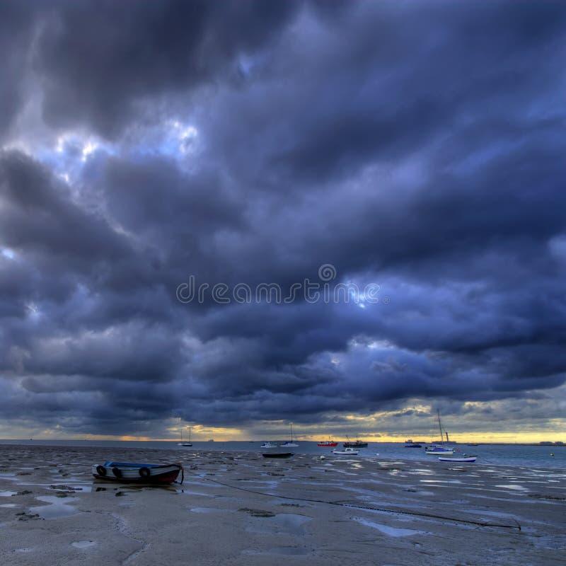Alba, spiaggia fangosa e barche fotografia stock libera da diritti