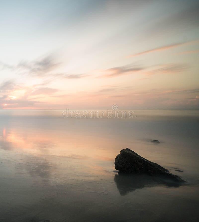 Alba splendida sopra un oceano calmo con una grande roccia nella priorità alta fotografia stock