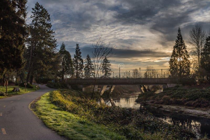 Alba sul fiume di Sammamish con un ponte sopra il fiume con la traccia pavimentata a sinistra in Redmond Washington fotografia stock