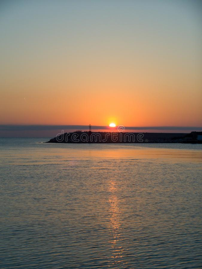 Alba sul mare adriatico, riflessioni della luce solare sull'acqua fotografia stock libera da diritti