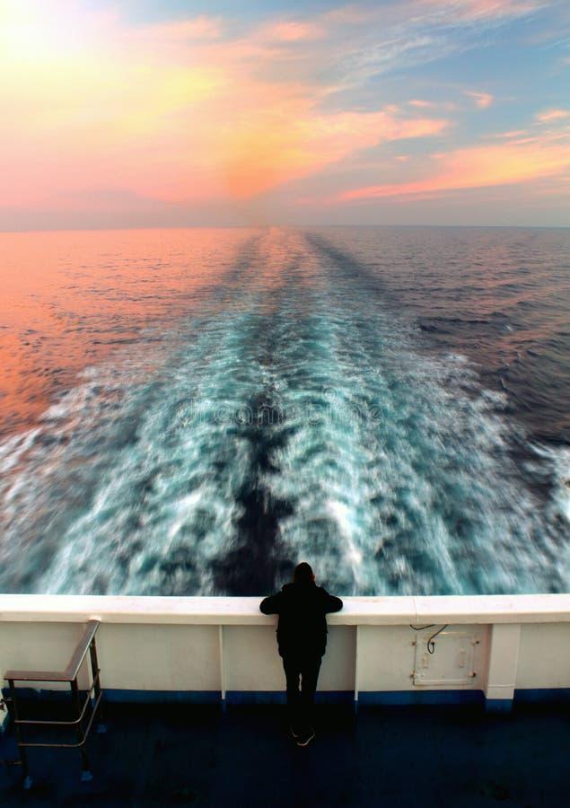Alba sul mare dalla poppa di una nave con una traccia dell'acqua immagine stock