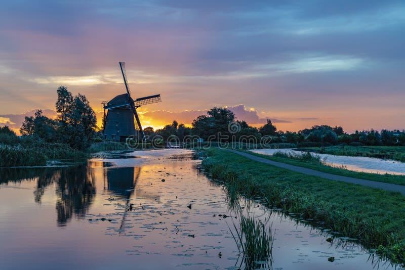 Alba sul mulino a vento olandese fotografie stock libere da diritti