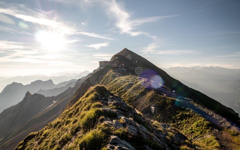 alba sul picco di montagna con la vista alla catena montuosa delle alpi svizzere, cresta della montagna dei sunflares fotografia stock