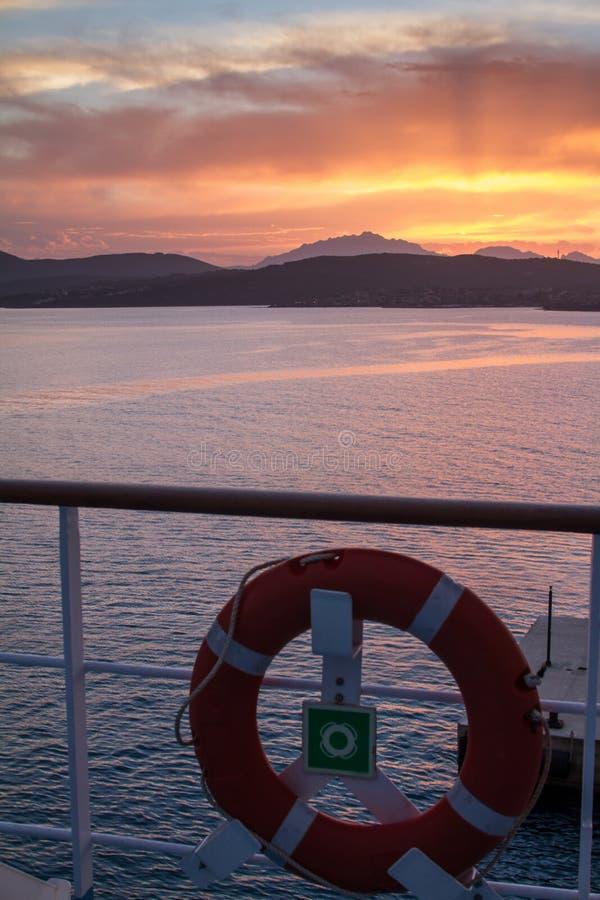 Alba sulla costa di mare sarda con colore arancio intenso visto dal mare sul traghetto che si accinge al bacino con il salvagente fotografie stock libere da diritti