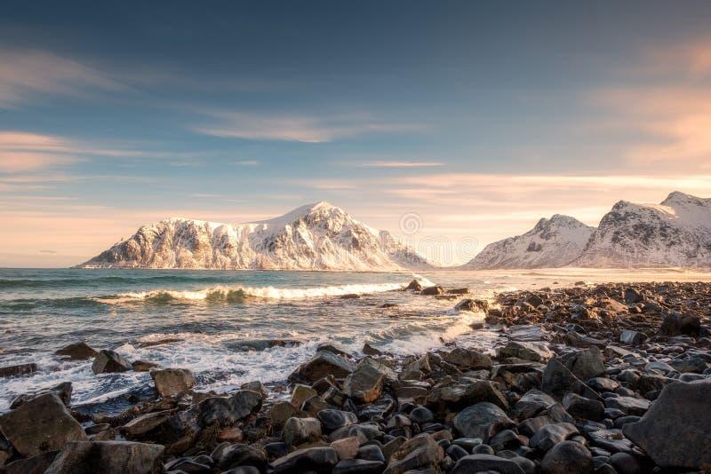 Alba sulla montagna della neve alla linea costiera in spiaggia di Skagsanden fotografie stock