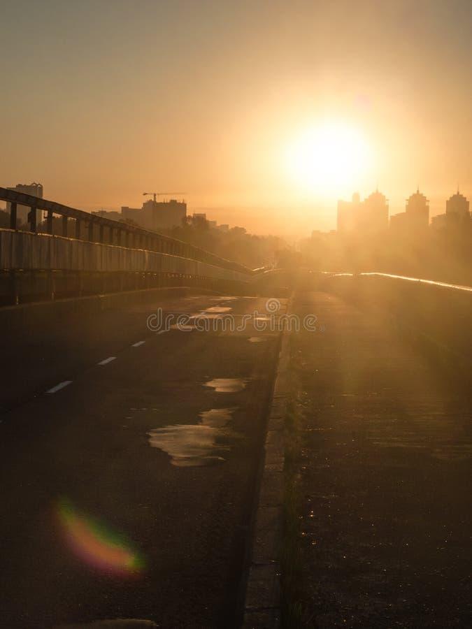 Alba sulla strada sul ponte verso il Sun Sole di mattina di abbagliamento fotografie stock