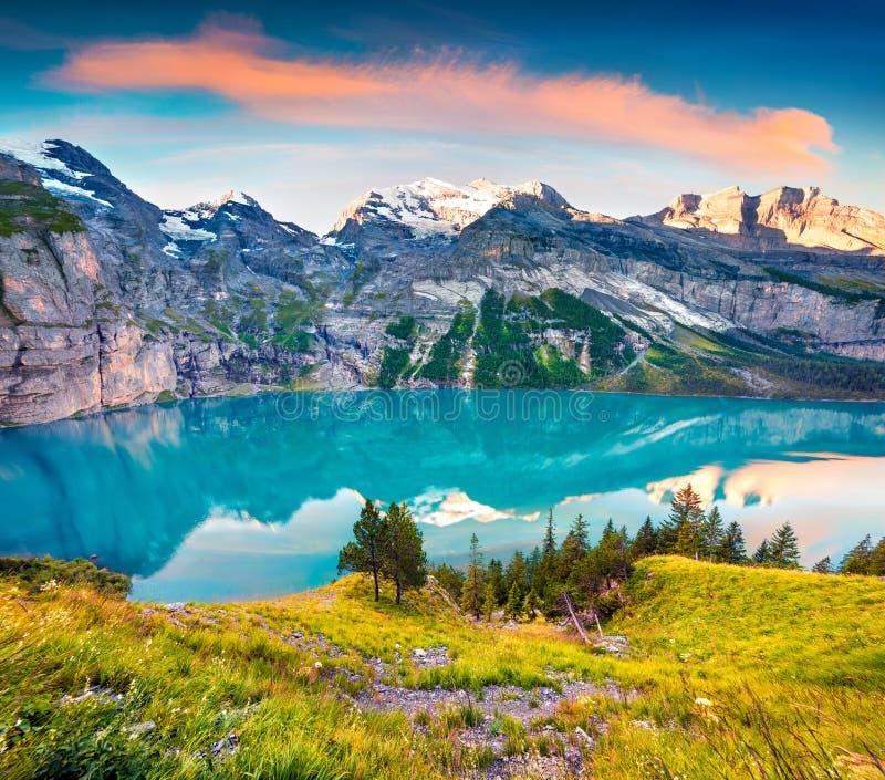 Alba variopinta di estate sul lago unico Oeschinensee Scena splendida di mattina nelle alpi svizzere con la montagna di Bluemlisa immagine stock libera da diritti
