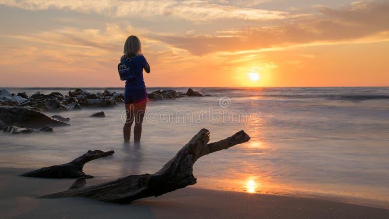 Alba veduta dalla sabbia, con la siluetta di una donna che fotografano alba, pietre che lasciano il mare e di un ceppo sepolto in immagini stock