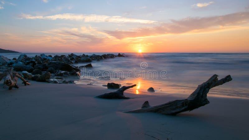 Alba veduta dalla sabbia, dalle pietre che lasciano il mare e da un ceppo sepolto in sabbia sulla riva del mar Mediterraneo fotografia stock libera da diritti