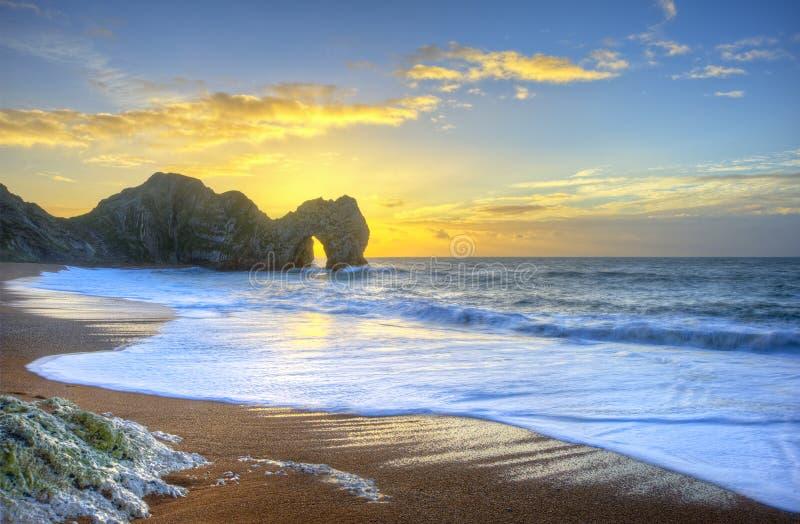 Alba vibrante sopra l'oceano con la pila della roccia in priorità alta fotografie stock