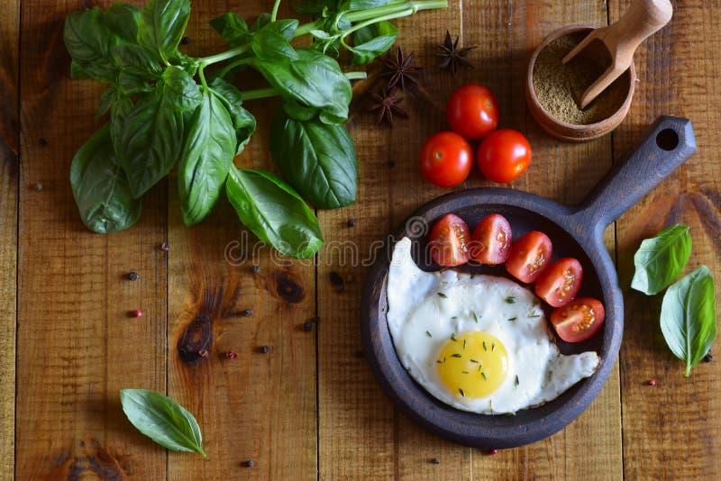 Albahaca, especias, tomates y un sartén con un huevo en la tabla fotografía de archivo libre de regalías