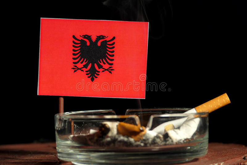 Albanese die vlag met het branden van sigaret in asbakje op zwarte wordt geïsoleerd royalty-vrije stock fotografie