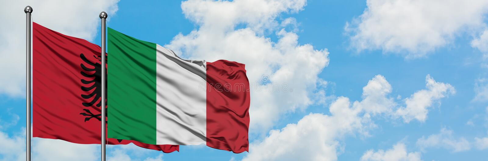 Albania and Italy flag waving in the wind against white cloudy blue sky together. Diplomacy concept, international relations. Peace, agreement, anthem royalty free stock image