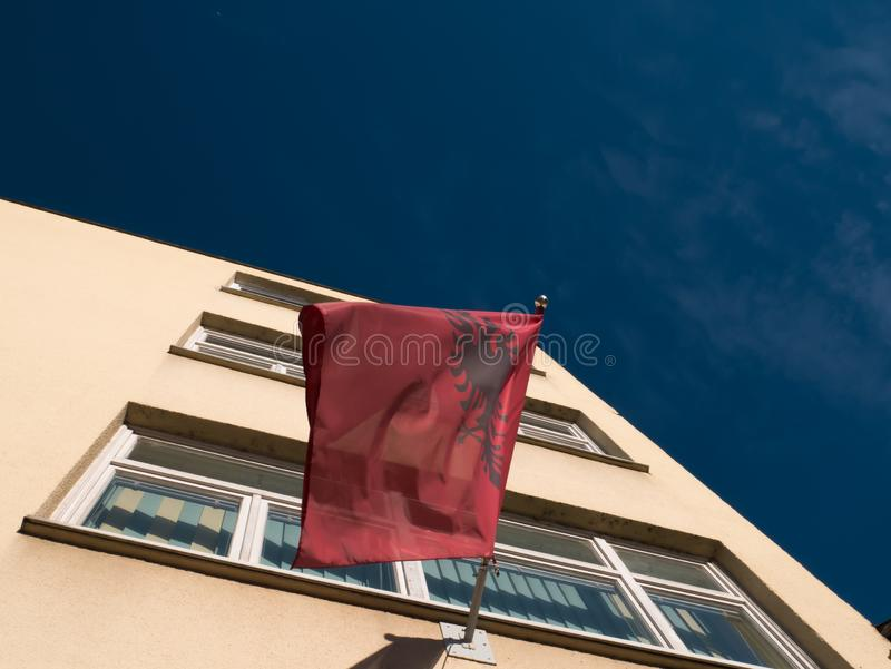Albanian flag on a building. The Albanian flag is blowing in the wind. In the background is a building stock photo