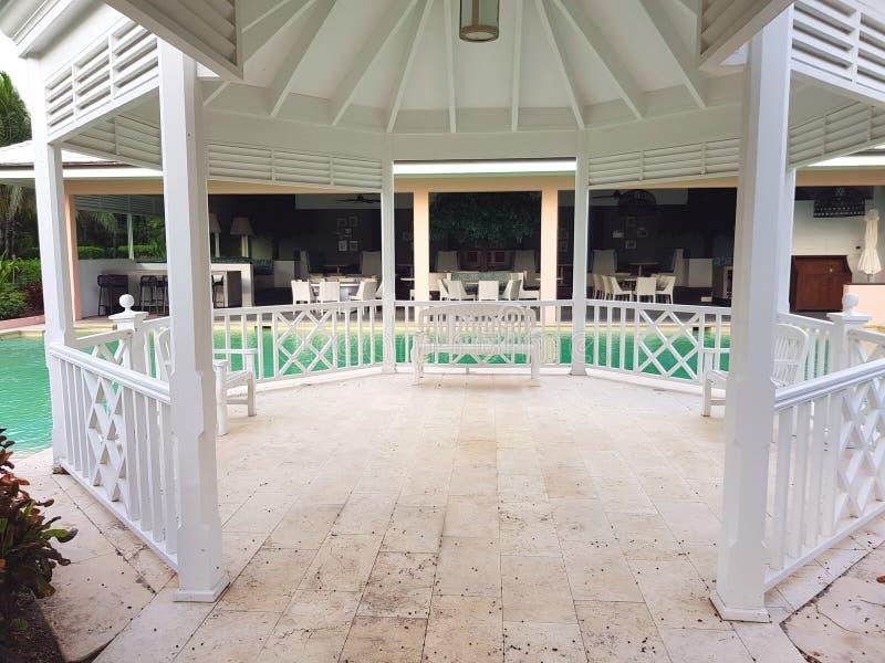ALBANY, NASSAU LES BAHAMAS - 21 JUILLET 2018 Banc blanc, belvédère dans une piscine dans le jardin d'un lieu de villégiature luxu photo libre de droits