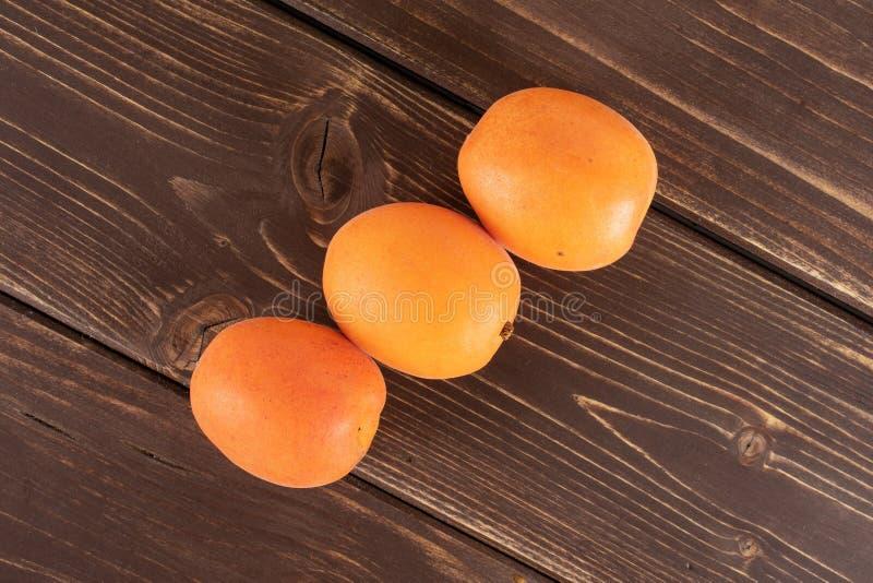 Albaricoque anaranjado fresco en la madera marrón imagen de archivo
