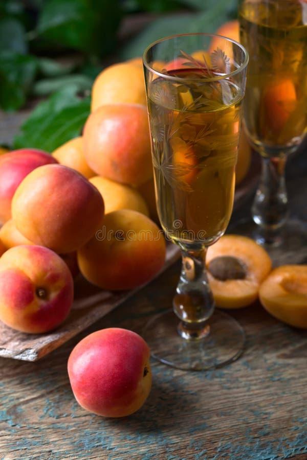 Albaricoques jugosos con las hojas y el vidrio de vino dulce imagen de archivo libre de regalías