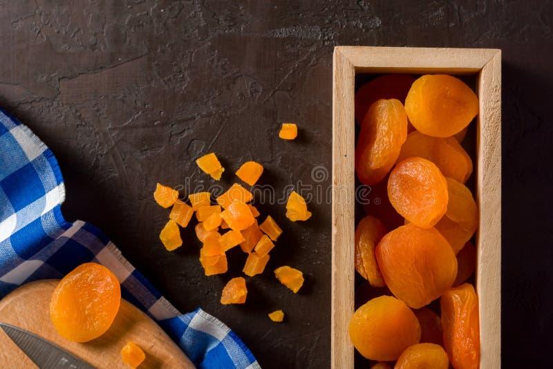 Albaricoques secados deliciosos y sanos Secado recientemente En un fondo marrón en caja de madera foto de archivo