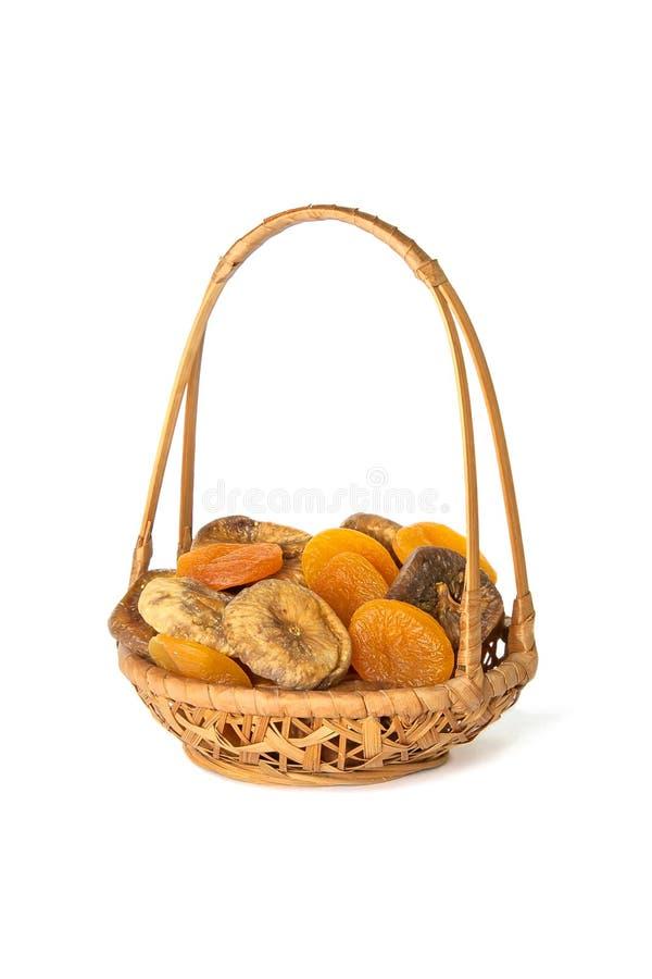 Albaricoques secados e higos en una cesta de mimbre aislada en blanco foto de archivo libre de regalías