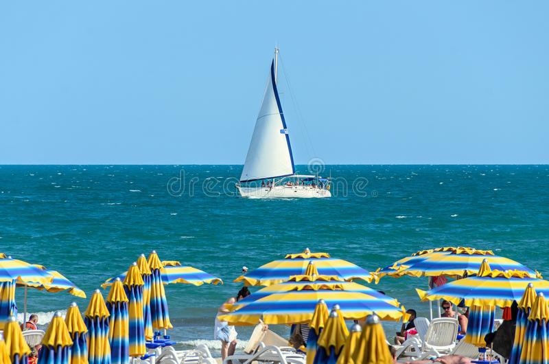 ALBENA, BULGARIA - JUNE 17, 2017: Wind boat yacht on blue Black Sea water near beach with tourists. stock image