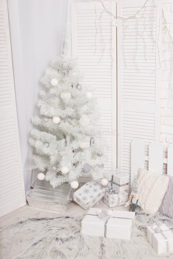 Alberi di Natale con il mucchio dei contenitori di regalo sopra fondo bianco, interno, nuovo anno fotografia stock libera da diritti